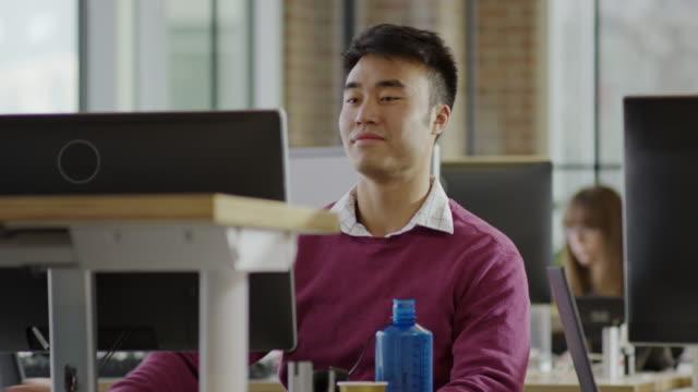 medium panning shot of businessman sitting at desk / lehi, utah, united states - lehi stock-videos und b-roll-filmmaterial