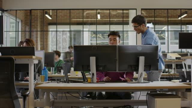 Medium panning shot of businessmen working together in office / Lehi, Utah, United States