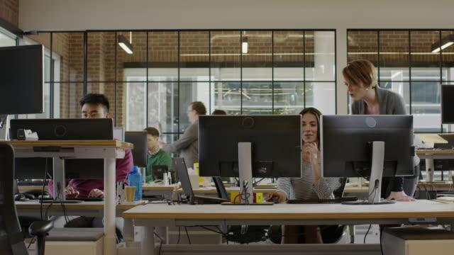 medium panning shot of businesswomen working together in office / lehi, utah, united states - desk stock videos & royalty-free footage