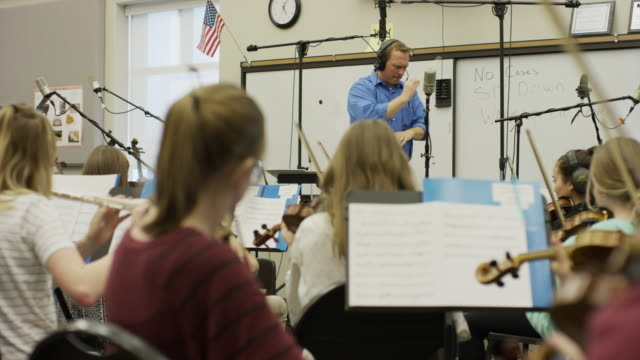 medium panning shot of conductor leading school orchestra / american fork, utah, united states - performance group stock videos & royalty-free footage