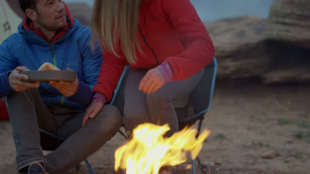 Medium panning shot of couple at campfire in desert / Moab, Utah, United States