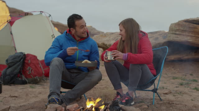 medium panning shot of couple at campfire in desert / moab, utah, united states - moab utah stock-videos und b-roll-filmmaterial