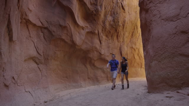 medium panning shot of couple hiking in narrow canyon / escalante, utah, united states - escalante stock-videos und b-roll-filmmaterial