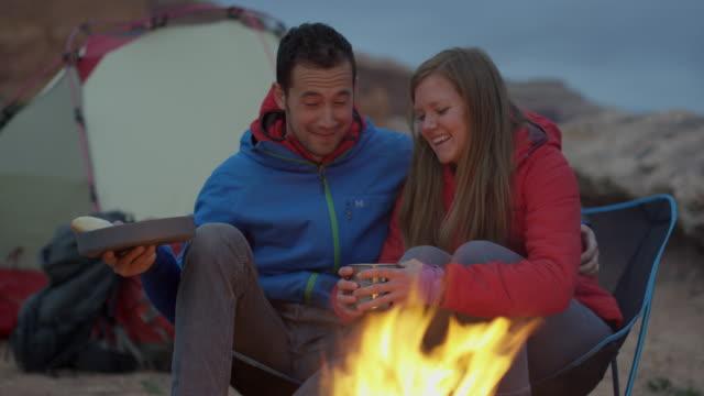 Medium panning shot of couple kissing at campfire in desert / Moab, Utah, United States