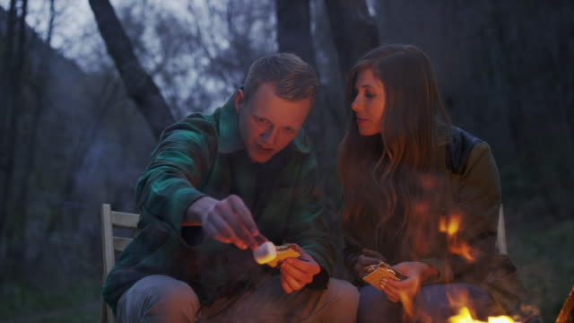 medium panning shot of couple making s‰'mores at campfire / american fork canyon, utah, united states - american fork canyon stock videos and b-roll footage
