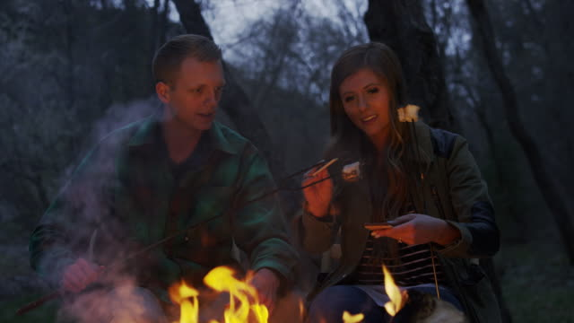 medium panning shot of couple making s'mores at campfire / american fork canyon, utah, united states - american fork canyon stock videos and b-roll footage
