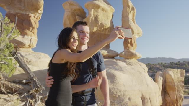 medium panning shot of couple posing for selfie in desert / escalante, utah, united states - escalante stock-videos und b-roll-filmmaterial
