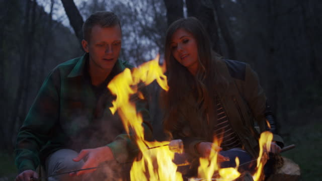 medium panning shot of couple roasting marshmallows at campfire / american fork canyon, utah, united states - american fork canyon stock videos and b-roll footage