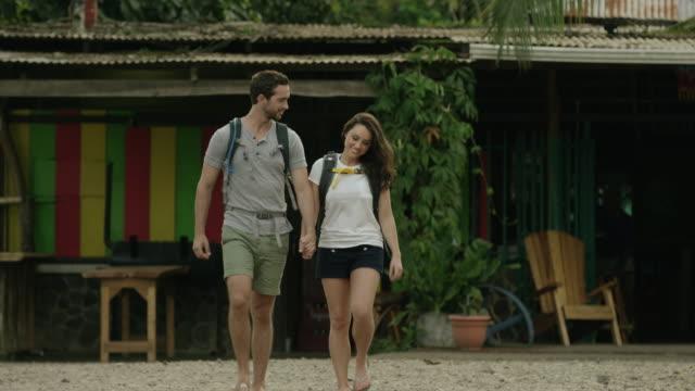 Medium panning shot of couple walking in village / Esterillos, Puntarenas, Costa Rica