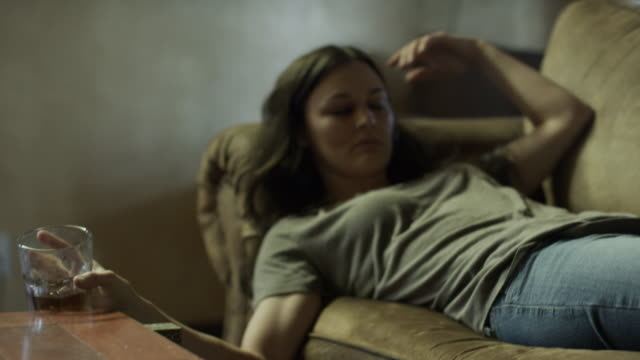 vidéos et rushes de medium panning shot of drunk woman laying on sofa holding glass / springville, utah, united states - springville utah