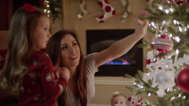 "stockvideo's en b-roll-footage met ""medium panning shot of family decorating christmas tree / cedar hills, utah, united states"" - kerstboom versieren"