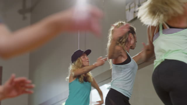 medium panning shot of fitness instructor leading exercise class / orem, utah, united states - weitere themen stock-videos und b-roll-filmmaterial