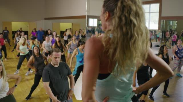 vídeos de stock, filmes e b-roll de medium panning shot of fitness instructor leading exercise class / orem, utah, united states - outro tema