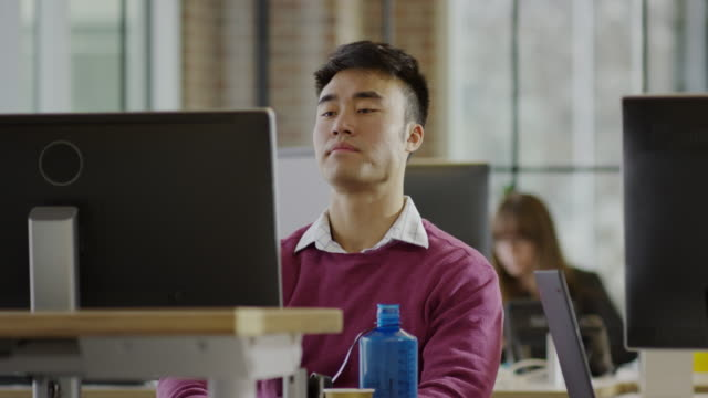 vidéos et rushes de medium panning shot of frustrated businessman working at desk / lehi, utah, united states - frustration
