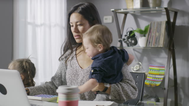 vidéos et rushes de medium panning shot of frustrated mother working at desk with children / cedar hills, utah, united states - surchargé de travail