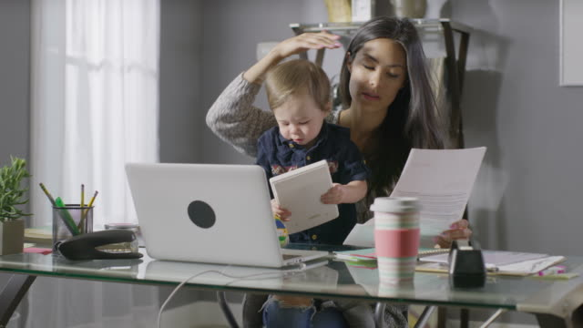 Medium panning shot of frustrated mother working at desk with son in lap / Cedar Hills, Utah, United States