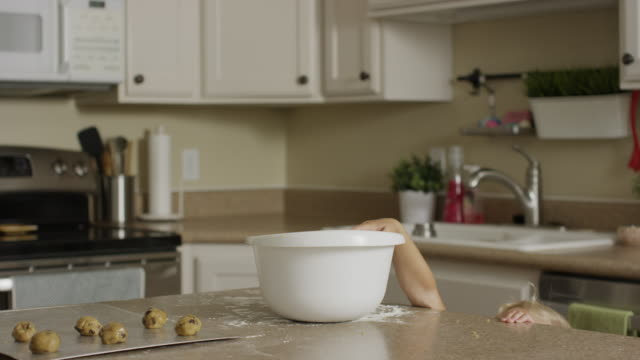 vídeos de stock, filmes e b-roll de medium panning shot of girl taking cookie dough from bowl in kitchen / orem, utah, united states - orem