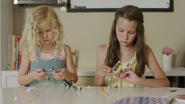 medium panning shot of girls assembling models of molecules / orem, utah, united states - orem utah stock videos & royalty-free footage
