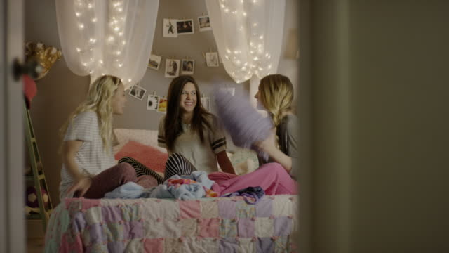 medium panning shot of girls having pillow fight in bedroom / cedar hills, utah, united states - 枕投げ点の映像素材/bロール