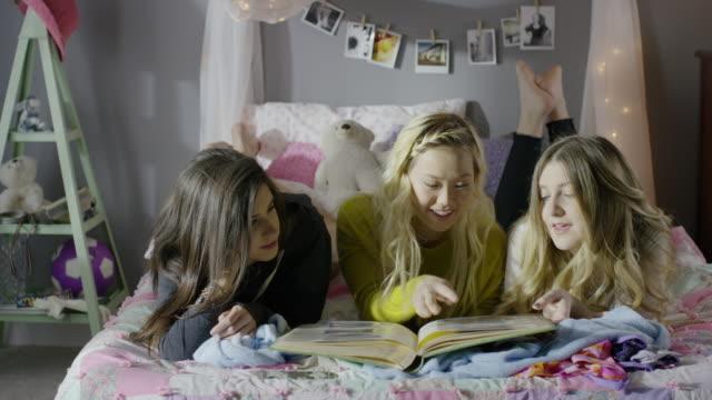 vidéos et rushes de medium panning shot of girls looking at photo album in bedroom / cedar hills, utah, united states - regarder