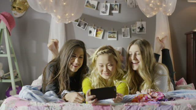 medium panning shot of girls using cell phone in bedroom / cedar hills, utah, united states - portable information device stock videos & royalty-free footage