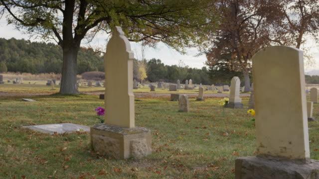 Medium panning shot of gravestones in cemetery / Spring City, Utah, United States
