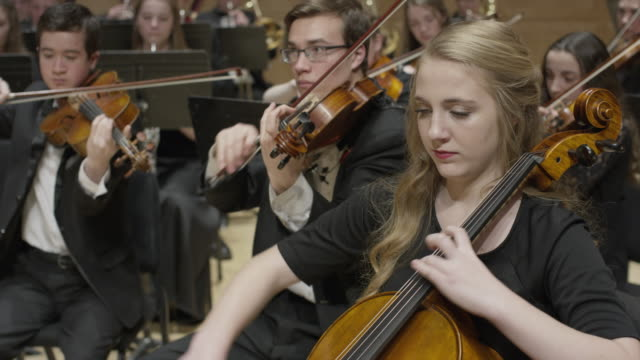 medium panning shot of high school orchestra performing on stage / salt lake city, utah, united states - orchestra stock videos & royalty-free footage
