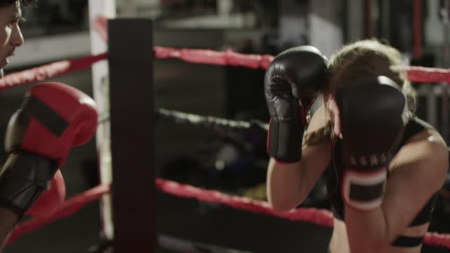 Medium panning shot of male and female boxers sparring / Lehi, Utah, United States