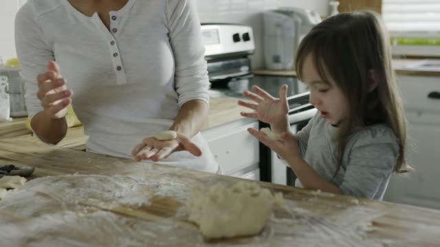 medium panning shot of mother and daughter baking cookies in kitchen / provo, utah, united states - dotter bildbanksvideor och videomaterial från bakom kulisserna