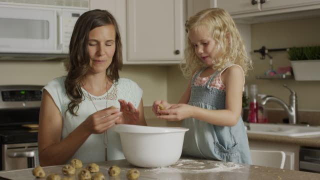 vídeos y material grabado en eventos de stock de medium panning shot of mother and daughter rolling cookie dough / orem, utah, united states - concentración