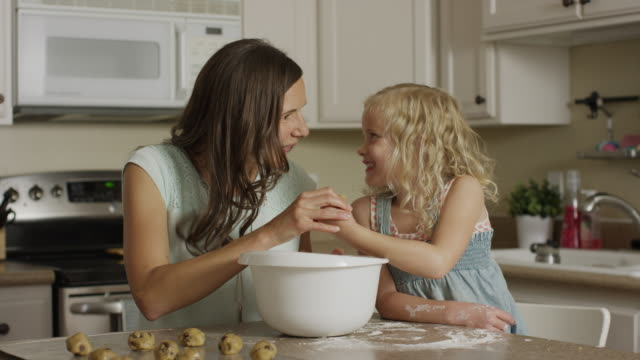 medium panning shot of mother and daughter rolling cookie dough / orem, utah, united states - orem utah stock videos & royalty-free footage