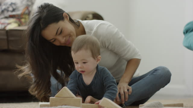 stockvideo's en b-roll-footage met medium panning shot of mother and son playing with blocks on floor / provo, utah, united states - provo