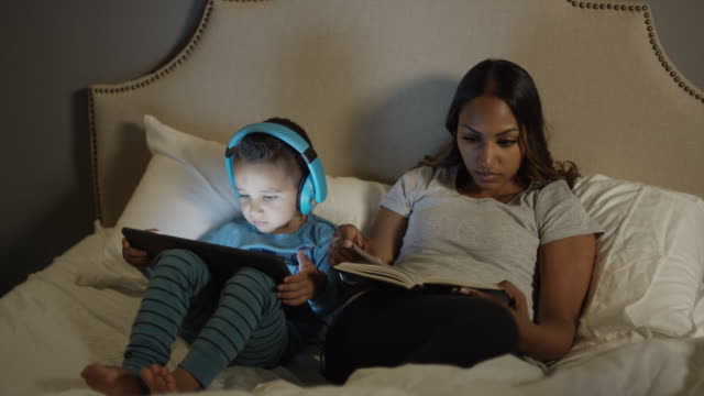 Medium panning shot of mother and son reading book and e-book on bed / Cedar Hills, Utah, United States