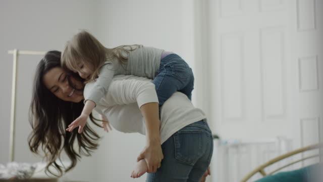 stockvideo's en b-roll-footage met medium panning shot of mother carrying daughter piggyback / provo, utah, united states - provo