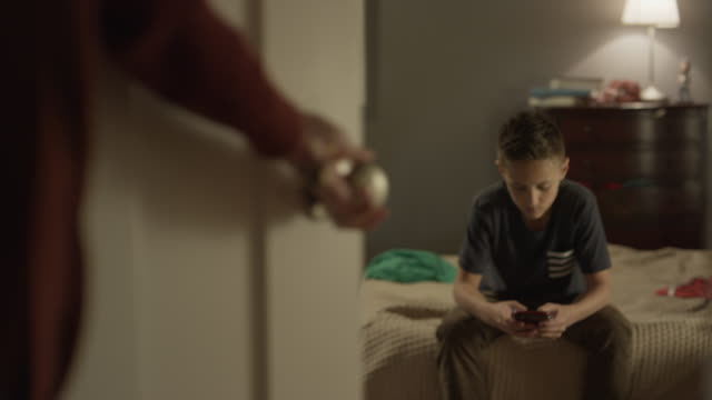 Medium panning shot of mother catching son using cell phone in bedroom / Cedar Hills, Utah, United States