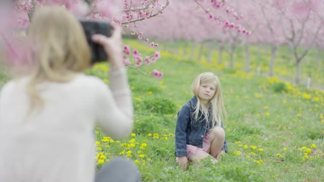 vídeos y material grabado en eventos de stock de medium panning shot of mother photographing daughter in park / alpine, utah, united states - falda