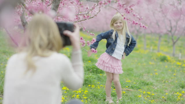 medium panning shot of mother photographing daughter in park / alpine, utah, united states - photographing stock videos and b-roll footage