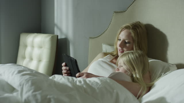 Medium panning shot of mother reading e-book to daughter in bed / Cedar Hills, Utah, United States