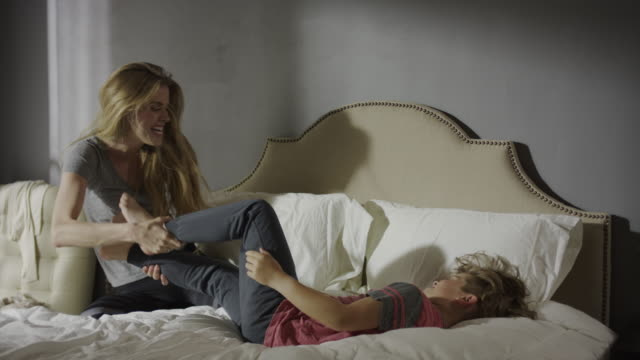 medium panning shot of mother tickling son on bed / cedar hills, utah, united states - tickling stock videos & royalty-free footage