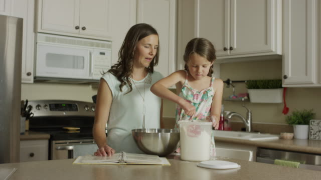 medium panning shot of mother watching daughter scoop flour into bowl / orem, utah, united states - mixing bowl stock videos and b-roll footage
