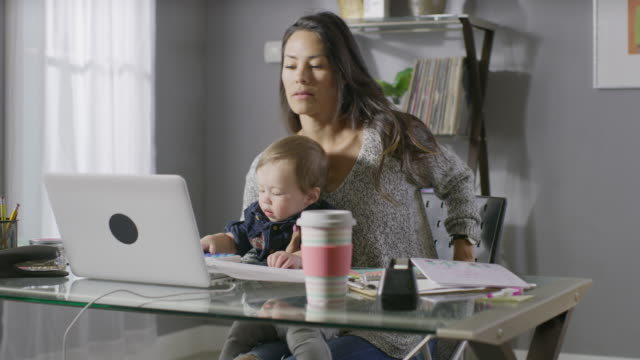 vídeos de stock e filmes b-roll de medium panning shot of mother working at desk caring for son and daughter / cedar hills, utah, united states - multitarefas