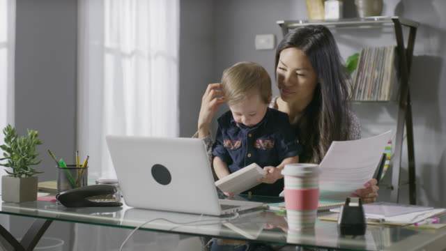 medium panning shot of mother working at desk with son in lap / cedar hills, utah, united states - multitasking stock videos & royalty-free footage
