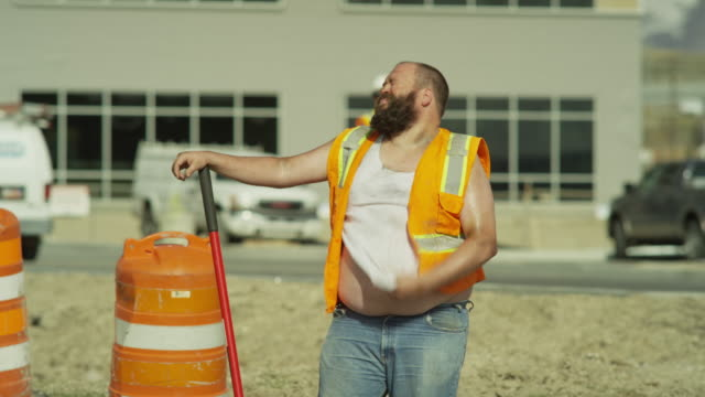 medium panning shot of overweight construction worker sweating / lehi, utah, united states - 疲れている点の映像素材/bロール