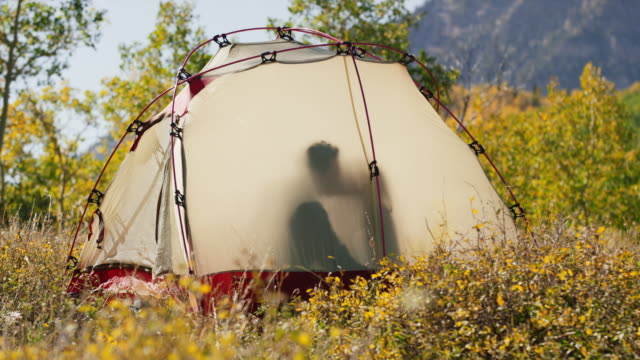vídeos y material grabado en eventos de stock de medium panning shot of passionate couple kissing in translucent tent / american fork canyon, utah, united states - american fork canyon