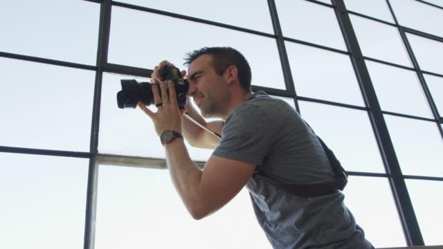 Medium panning shot of photographer and model near window / Draper, Utah, United States