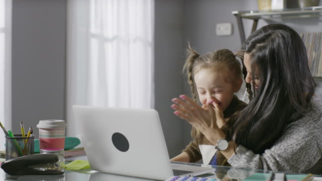 medium panning shot of smiling mother and daughter using laptop / cedar hills, utah, united states - part of a series stock-videos und b-roll-filmmaterial