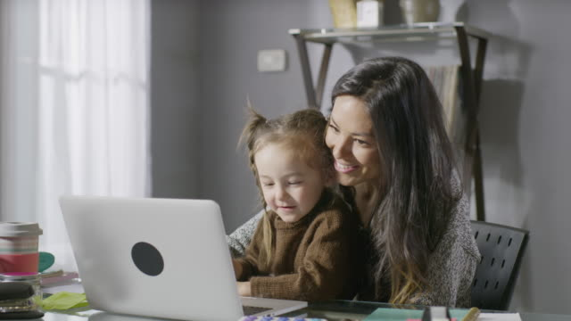 medium panning shot of smiling mother and daughter using laptop / cedar hills, utah, united states - laptop benutzen stock-videos und b-roll-filmmaterial