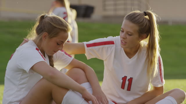 Medium panning shot of soccer player comforting crying teammate / Springville, Utah, United States
