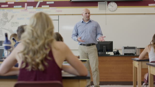 Medium panning shot of student asking question in high school science class / Mapleton, Utah, United States