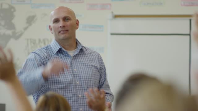 Medium panning shot of students asking teacher questions / Mapleton, Utah, United States